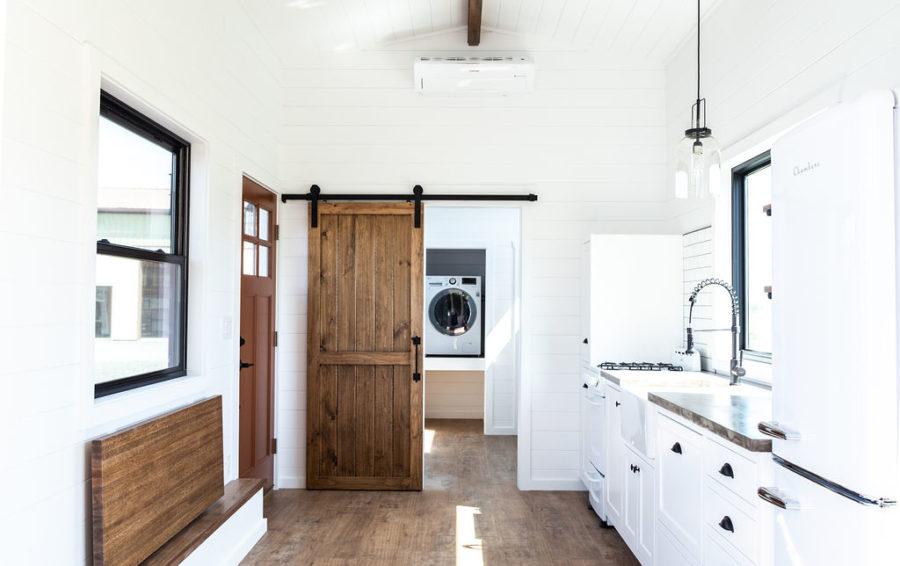 The bathroom is hidden behind a wooden barn door that's both beautiful and space-efficient