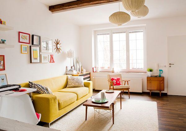 Home Essentials Living Room with Hardwood Floors and Paper Chandeliers Yellow Couch Wall Gallery