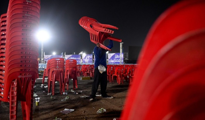 A man stacks chairs after a Palang Pracharath Party rally in the northeastern Thai province of Nakhon Ratchasima in March. Photo: AFP