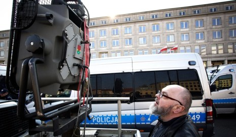 A protester looks at an acoustic crowd dispersal device during a demonstration outside Poland's ministry of economy building in Warsaw. Photo: Alamy