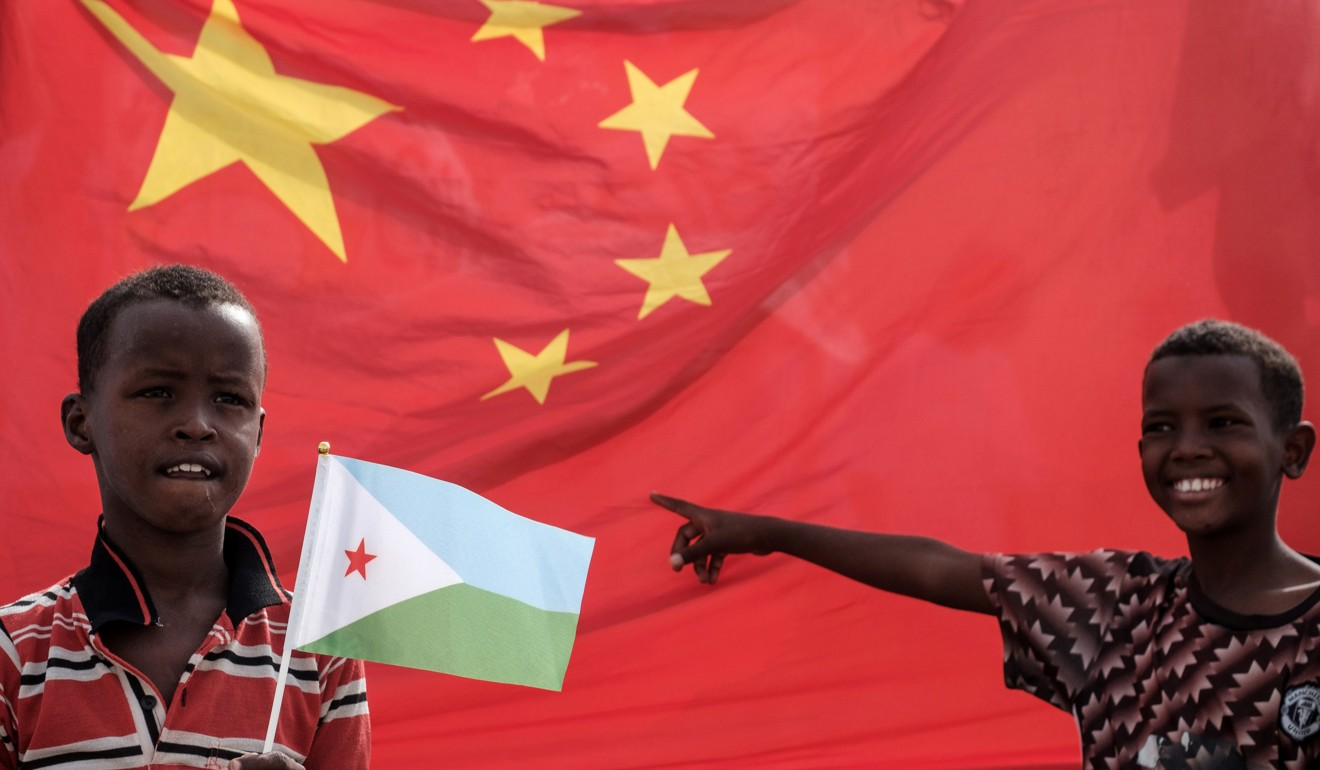 A boy holds Djiboutian national flag in front of Chinese national flag as he waits for Djibouti's President Ismail Omar Guellehas before the launching ceremony of new 1,000-unit housing construction project in Djibouti in 2018. Photo: AFP