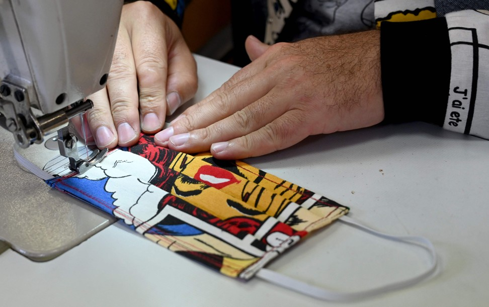 Aragovic works on one of his colourful masks. Photo: AFP