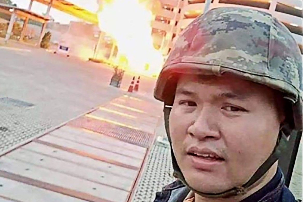 A screenshot from Jakrapanth Thomma's Facebook live stream shows him standing in front of a building on fire in the city of Nakhon Ratchasima on Saturday. Photo: Facebook via AFP