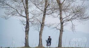 中国と北朝鮮の国境、鴨緑江の近くで自転車に座っている北朝鮮兵(2017年4月16日撮影)。(c)AFP/Johannes EISELE
