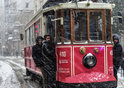 People stand on a tram in the snow in Turkey