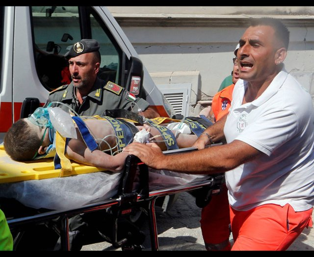 Rescue workers carry a child after an earthquake hit the island of Ischia, in Naples