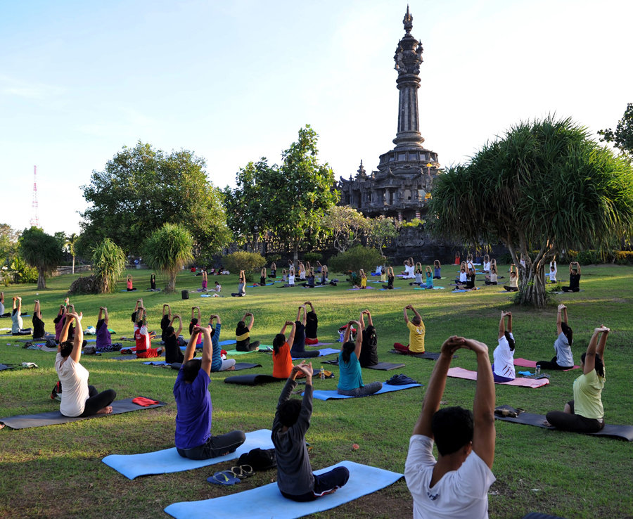 Locals take part in a yoga session near Denpasar's Bajra Sandhi monument