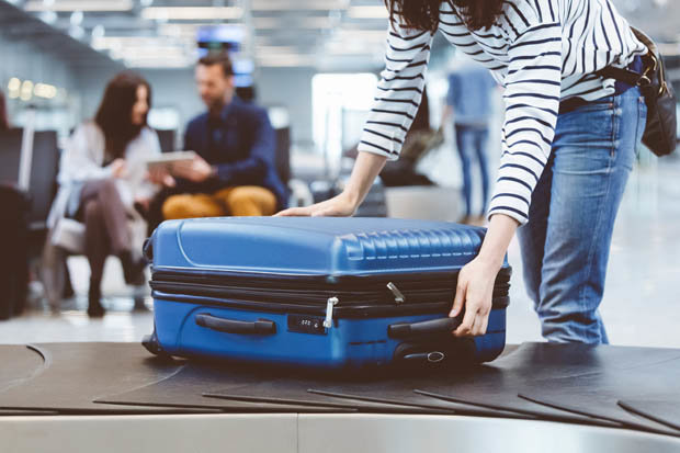 A woman opening her suitcase