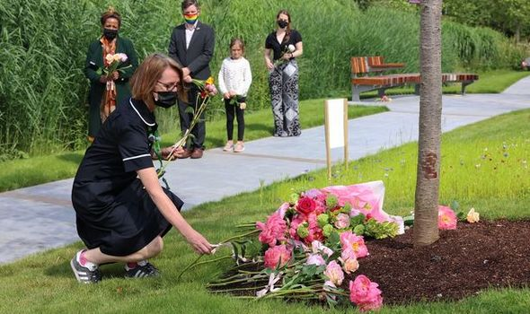 A nurse leaves a rose at Blossom Memorial Garden