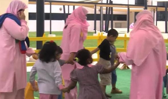 Dubai women play with their children