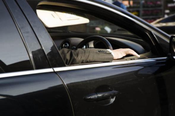 A man in a suit in a black car