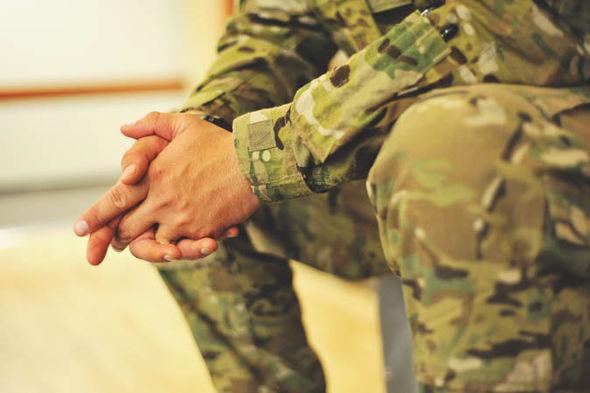 Soldier in uniform sitting down