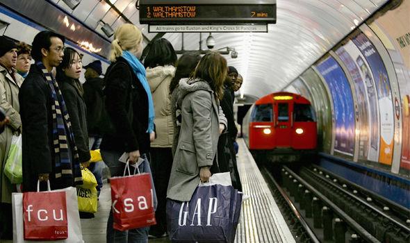 Passengers wait for a Tube train