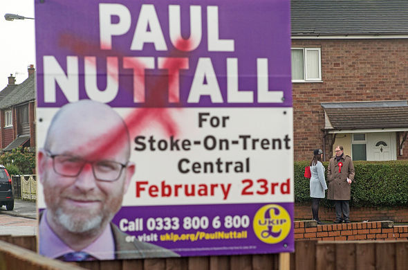Mr Snell stands in the background after a Ukip posted was defaced by vandals