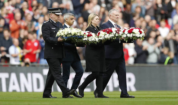 London Mayor Sadiq Khan lays a wreath on the pitch as respect for the victims