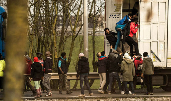 Migrants climb into the back of a lorry at Calais