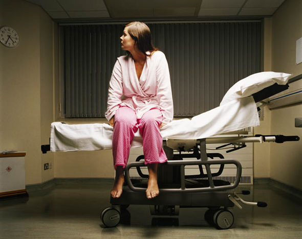 woman in pyjamas sitting on hospital bed
