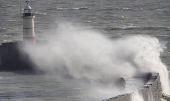 Fierce waves crash over the harbour wall at Newhaven