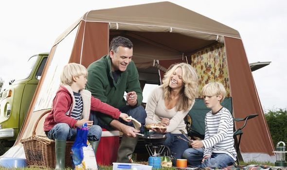 Family sits outside tent while camping