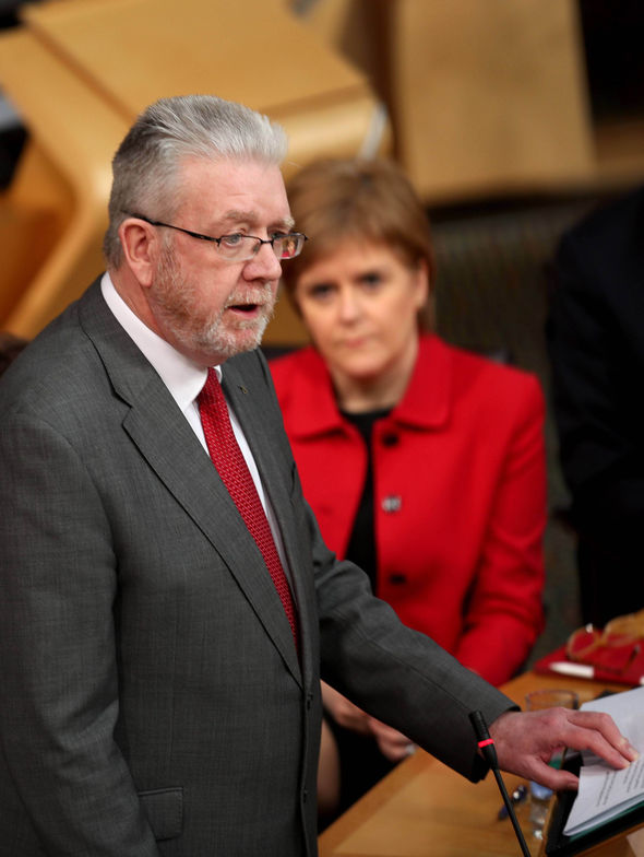 Mike Russell speaking with Nicola Sturgeon in background