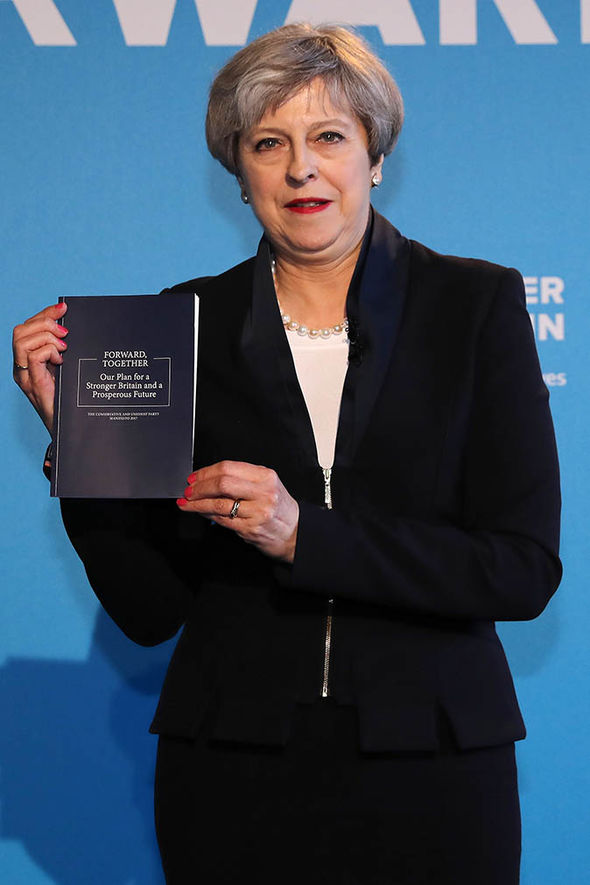 Theresa May holding the Tory manifesto