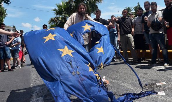 Greek protestors burn an EU flag