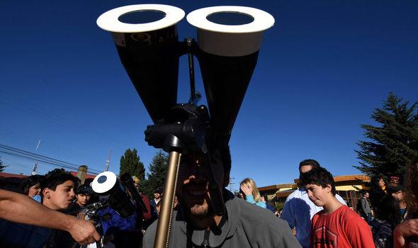 man observes a solar eclipse
