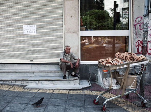 A street food vendor rests outside a polyclinic in Athens
