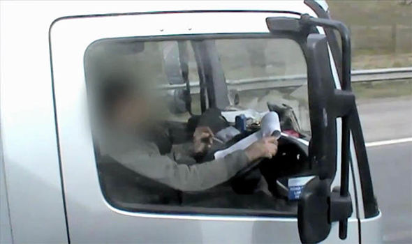 HGV lorry driver catching motorist making notes behind the wheel