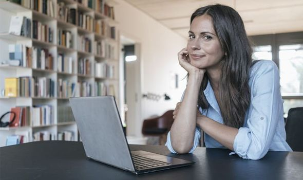 Woman sits at desk with laptop