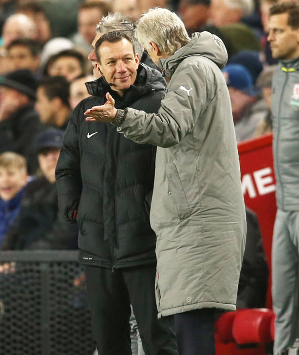 Arsene Wenger in conversation with fourth official Kevin Friend