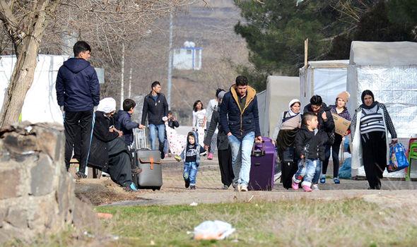 Yazidis refugees carry their belongings in Turkey