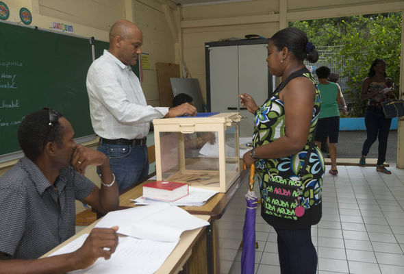 A voter casts her ballot in Pointe-à-Pitre, on the French Caribbean island of Guadeloupe