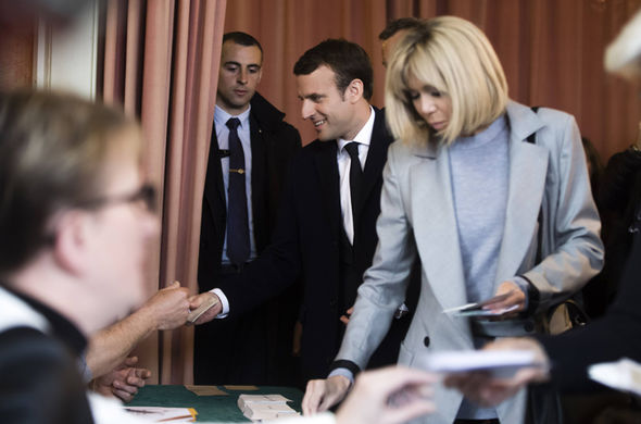 Emmanuel Macron (C) and his wife Brigitte Trogneux (R) vote in the first round of the election at the Town Hall of Le Touquet
