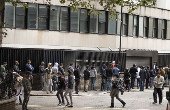Hundreds of migrants queuing outside an immigration centre in London