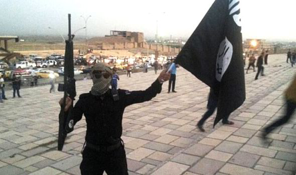 An Islamic State fighter brandishes the radical group's jet-black flag