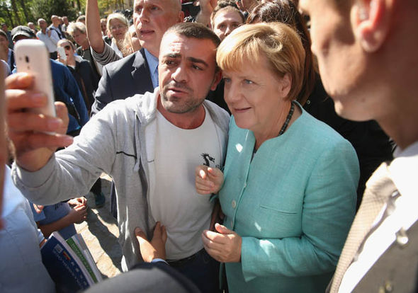 Image result for merkel with migrants taking selfies, photos