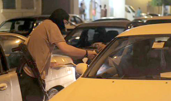 An ISIS fighter hands out propaganda in queuing traffic in Sirte