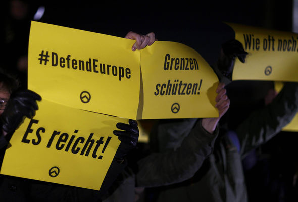 People are also holding placards with the logo of the far right Identitarian movement