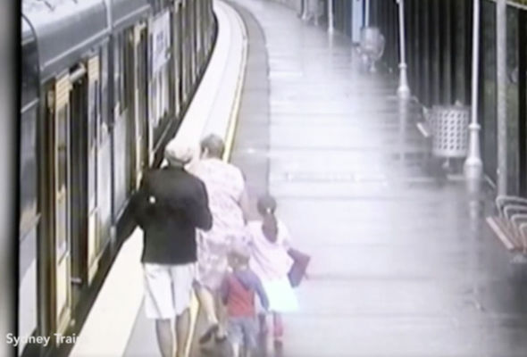 The boy is seen walking toward the train with his family