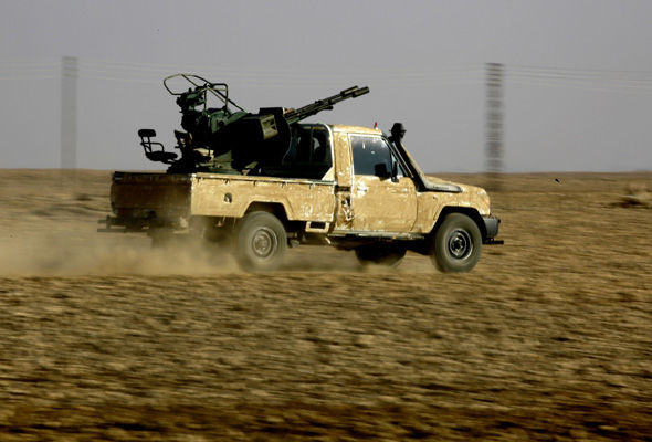 A fighter from the Syrian Democratic Forces drives on the outskirts of Raqqa