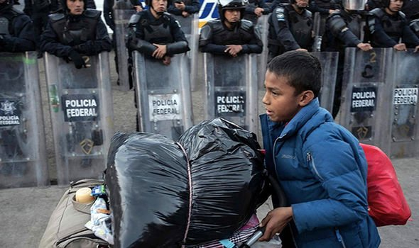 A boy travelling to the US carries his belongings while police officers look on