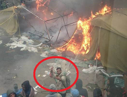 A migrant makes a 'V for Victory' sign as he takes a selfie in front of a burning tent
