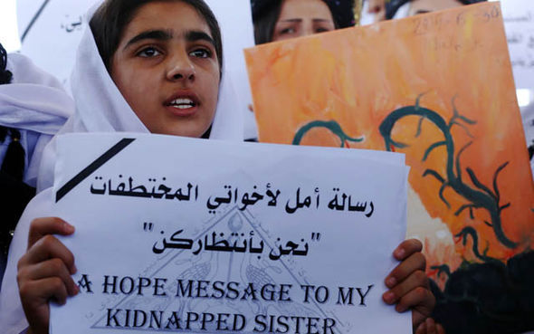 A Yazidi woman holds up a sign begging for news of her sister