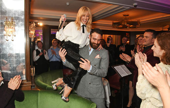 Joshua Sasse carrying Kylie Minogue