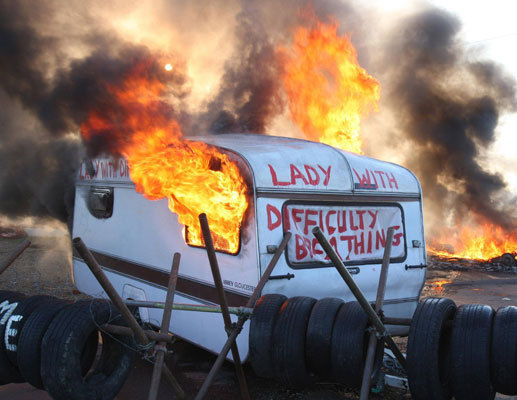 A caravan burns at Dale Farm in Essex where supporters have clashed with bailiffs