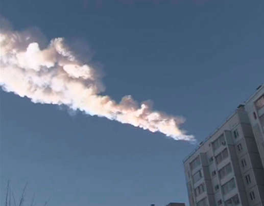 The trail of a falling object is seen above a residential apartment block in the Urals city of Chelyabinsk