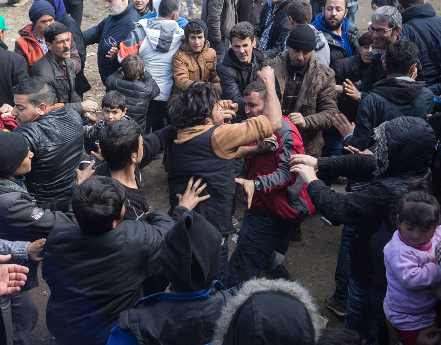 Desperate migrants fight each other as they scramble for food at the Greek border