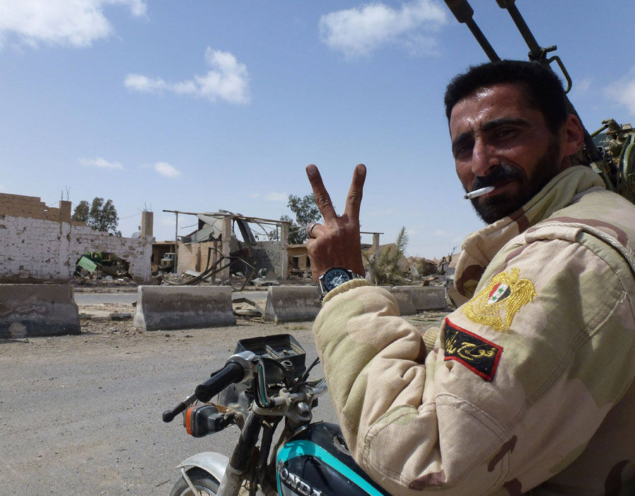 A member of the Syrian pro-government forces flashes the V-sign in a residential neighbourhood of the modern town of Palmyra