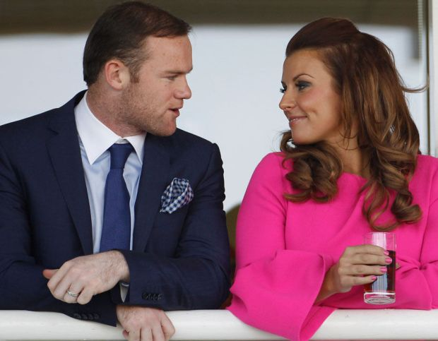 Manchester United football player Wayne Rooney and his wife Coleen watch the racing during the first day of the Aintree Grand National meeting on April 12, 2012